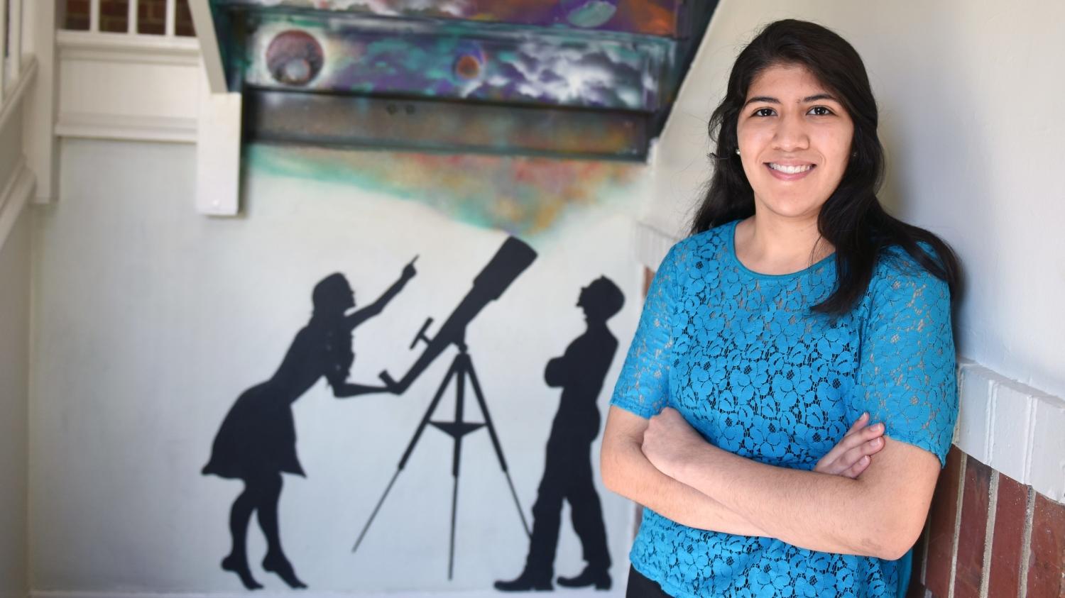 Paola Rivera in front of a painted silhouette of a man and woman at a telescope