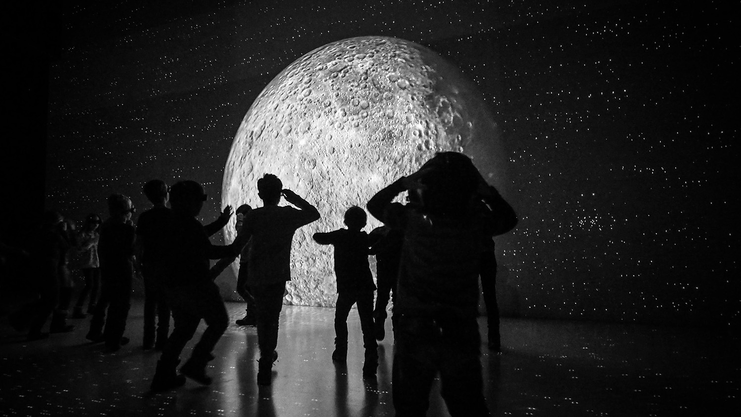 children silhouetted in front of a museum exhibit about the moon