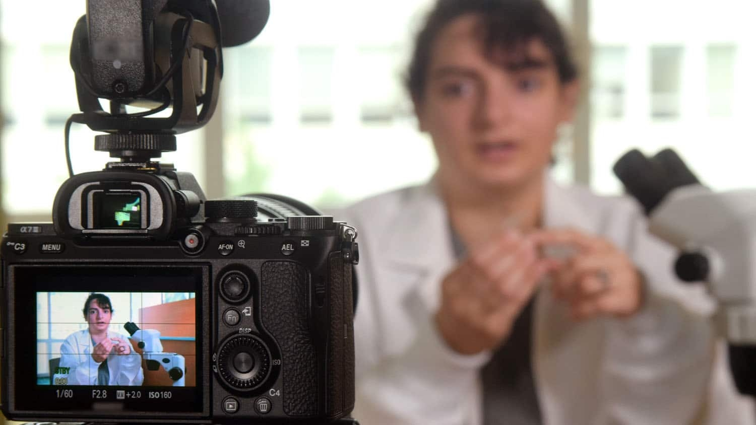 a camera is filming a scientist talking about her work; the scientist is also visible in the viewfinder of the camera